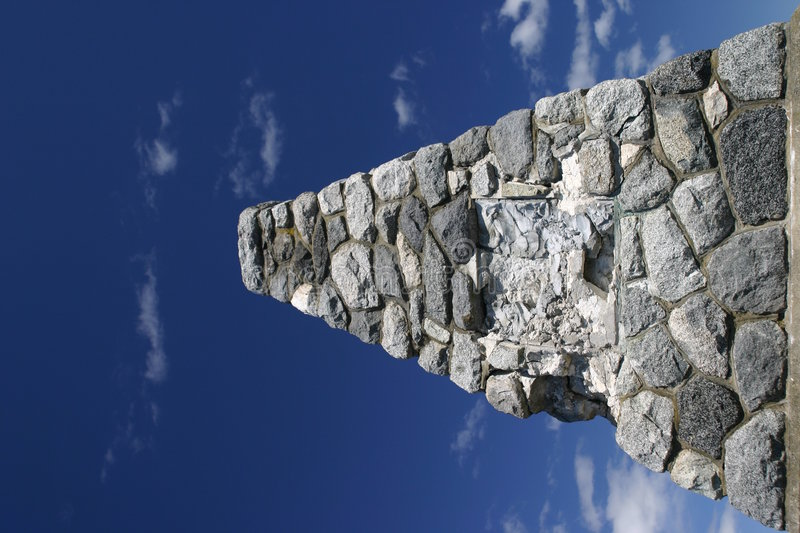 Cairn. Of rocks reach upwards into a blue sky with clouds stock photography