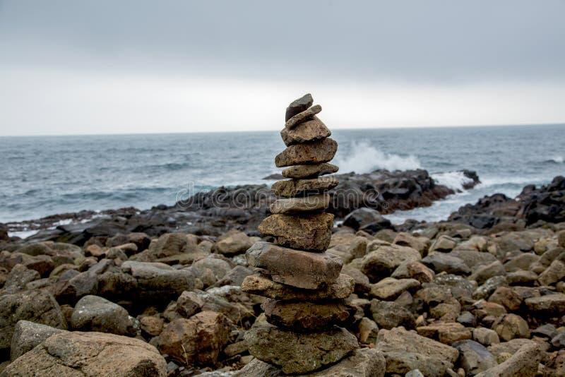 Cairn davanti a paesaggio costiero immagine stock