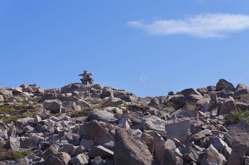 Cairn di Inukshuk sopra la collina di pietra contro cielo blu immagini stock libere da diritti