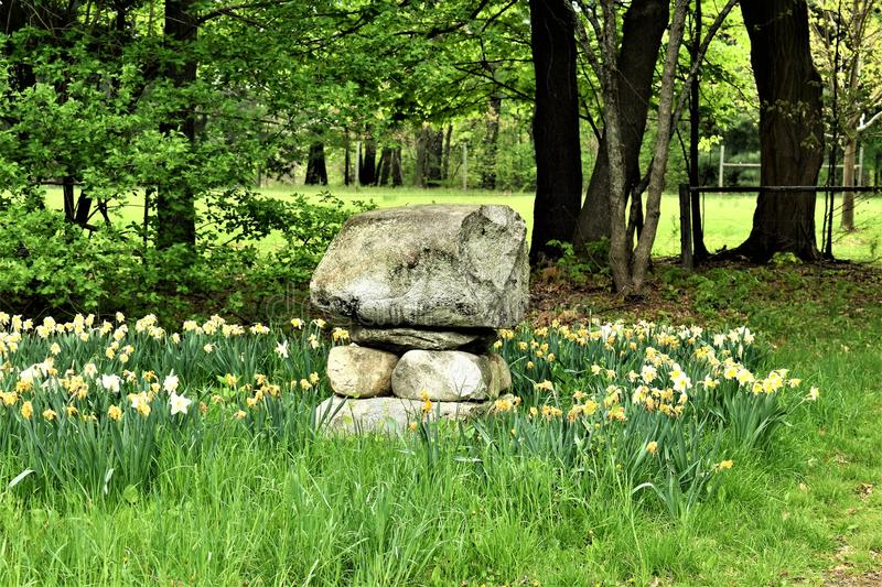 Cairn that flanks a cow pasteur in New England. Taken in Groton, Middlesex County, Massachusetts, United States. A scenic Spring view of a Cairn that flanks a stock images