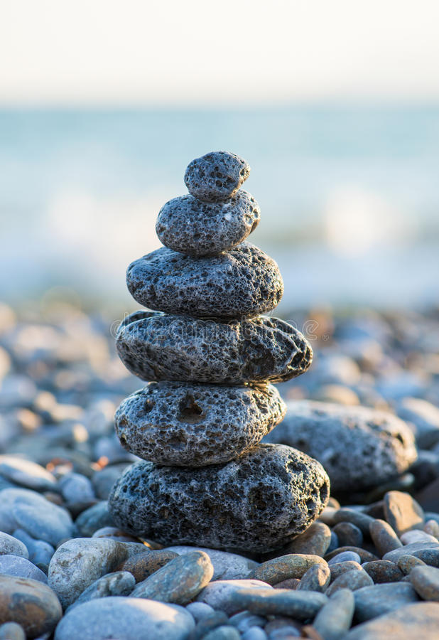 Cairn on the pebbly sea beach. Balanced stones, pebbles stacks against blue sea royalty free stock photo