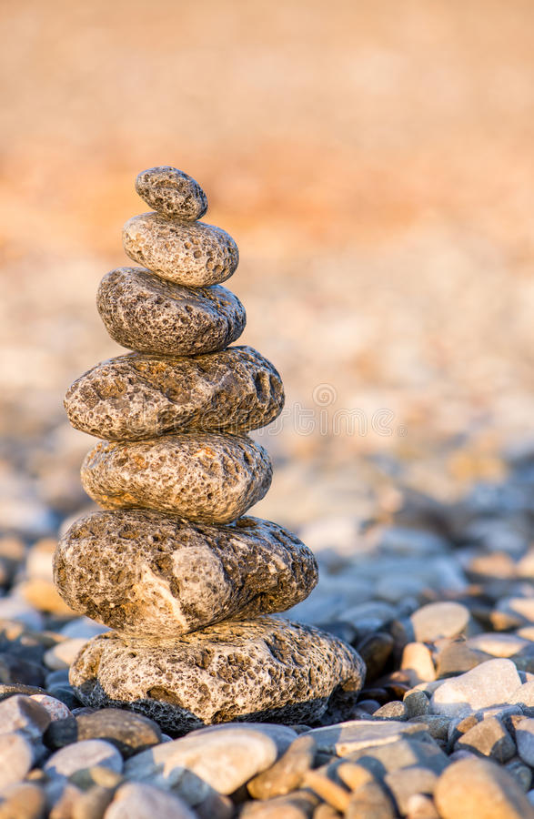 Cairn on the pebbly sea beach. Balanced stones, pebbles stacks against blue sea stock image
