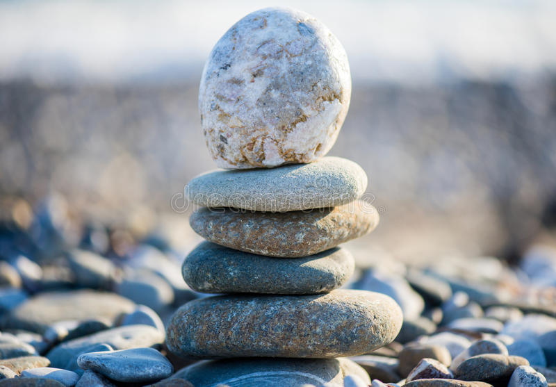 Cairn on the pebbly sea beach. Balanced stones, pebbles stacks against blue sea royalty free stock image
