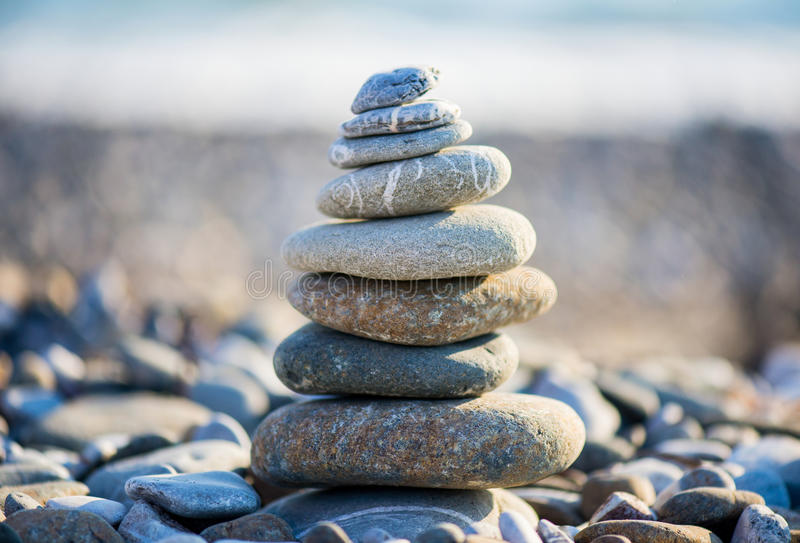 Cairn on the pebbly sea beach. Balanced stones, pebbles stacks against blue sea stock photo