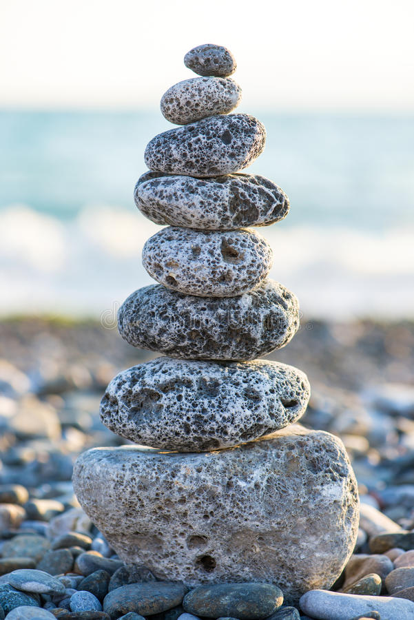 Cairn on the pebbly sea beach. Balanced stones, pebbles stacks against blue sea royalty free stock images