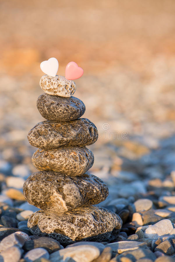 Cairn on the pebbly sea beach. Balanced stones, pebbles stacks against blue sea stock images