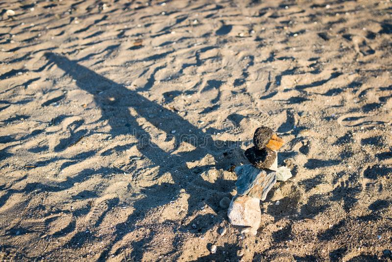 Cairn rock pile, long shadow. A cairn rock pile on a sandy beach casts a long shadow with the low natural sunlight stock photos