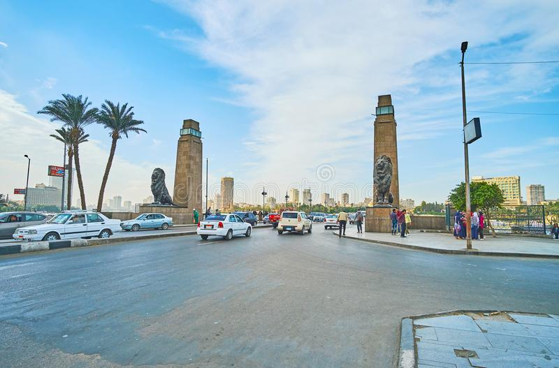 El Tahrir road, Cairo, Egypt. CAIRO, EGYPT - DECEMBER 24, 2017: The busy El Tahrir road, decorated with stone towers and sculprtures of lions at the entrance of royalty free stock photography