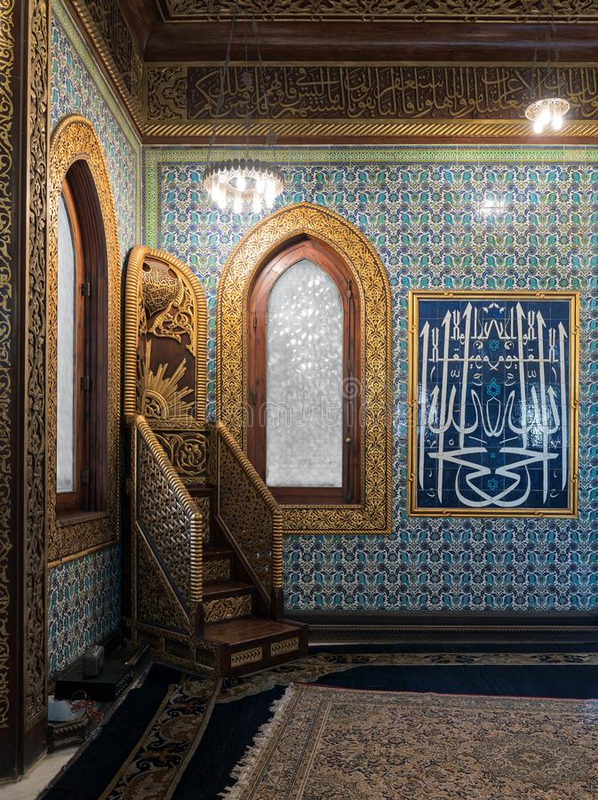 Wooden golden ornate minbar Platform, wooden arched window framed by golden ornate floral pattern, and Turkish ceramic tiles royalty free stock image