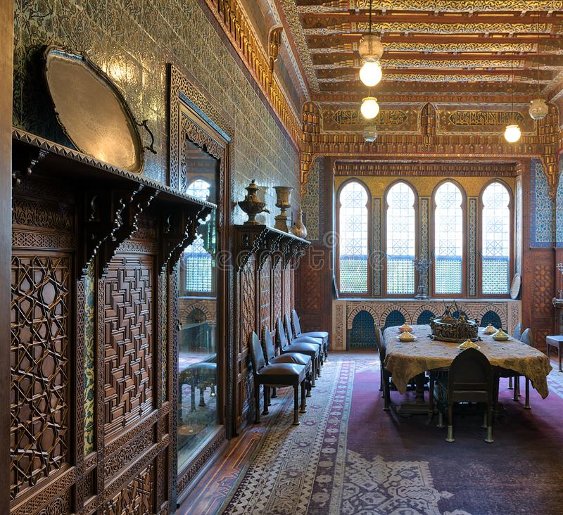 Manial Palace of Prince Mohammed Ali. Dining room at the Residence Building, with ornate wall and ceiling, Cairo, Egypt. Cairo, Egypt - December 2 2017: Manial royalty free stock photo