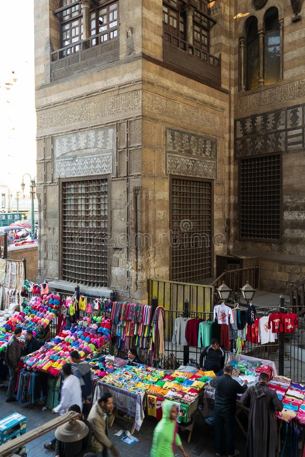 Clothes marked near old Sultan al Ghuri Mausoleum building, Cairo, Egypt. Cairo, Egypt- January 16 2016: Stalls with colorful clothes located outside old shabby royalty free stock photo