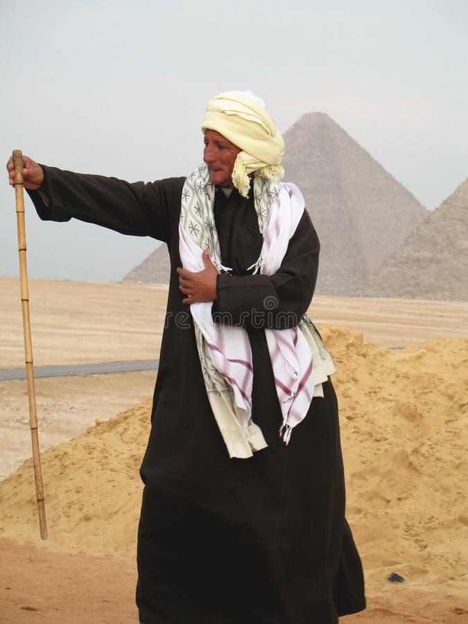 cairo Valle Egitto di Giza 5 gennaio 2008: L'uomo anziano in costume nazionale sta mostrando il bastone di bambù Le piramidi sono fotografia stock libera da diritti