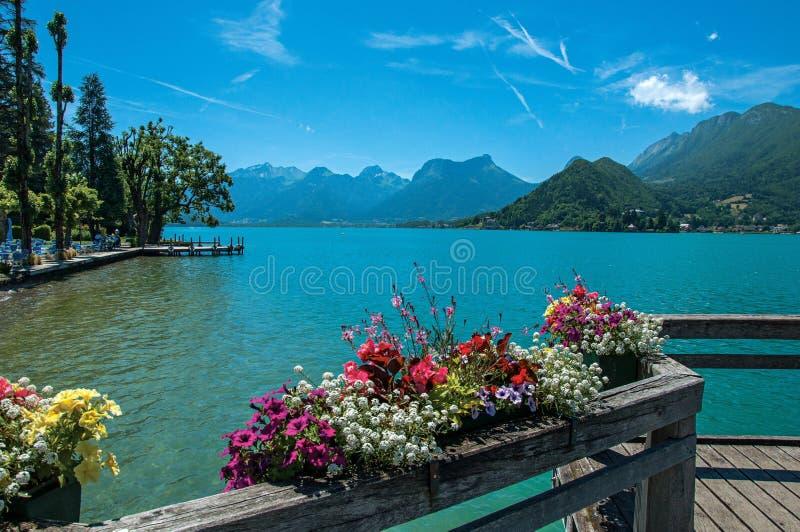Cais com as flores no lago de Annecy, na vila de Talloires imagem de stock