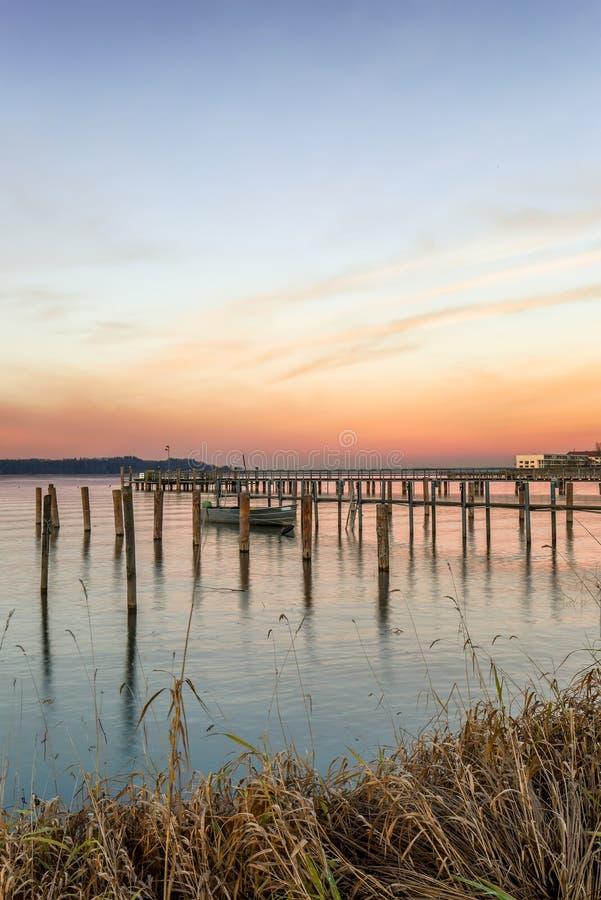 Cais com um barco no lago Chiemsee imagens de stock
