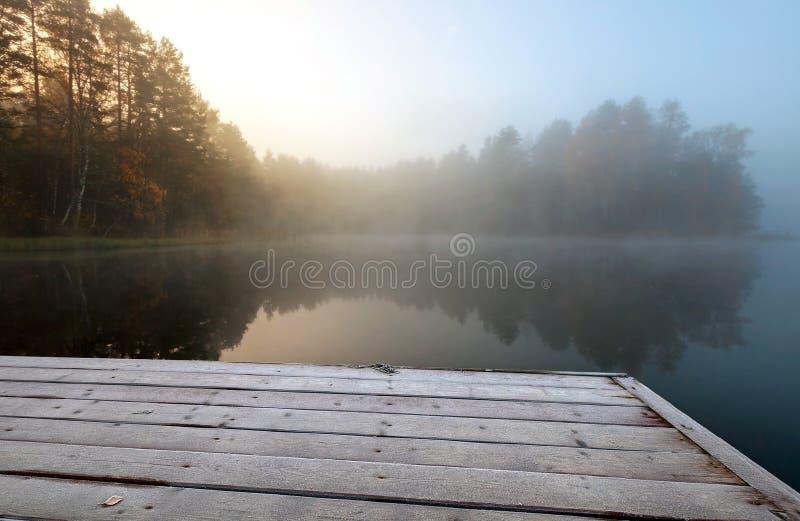 Cais congelado no lago na manhã nevoenta do frio ainda fotos de stock