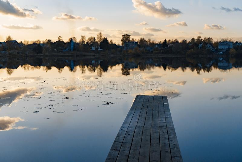 Cais de madeira com as folhas no lago quieto no outono fotografia de stock royalty free