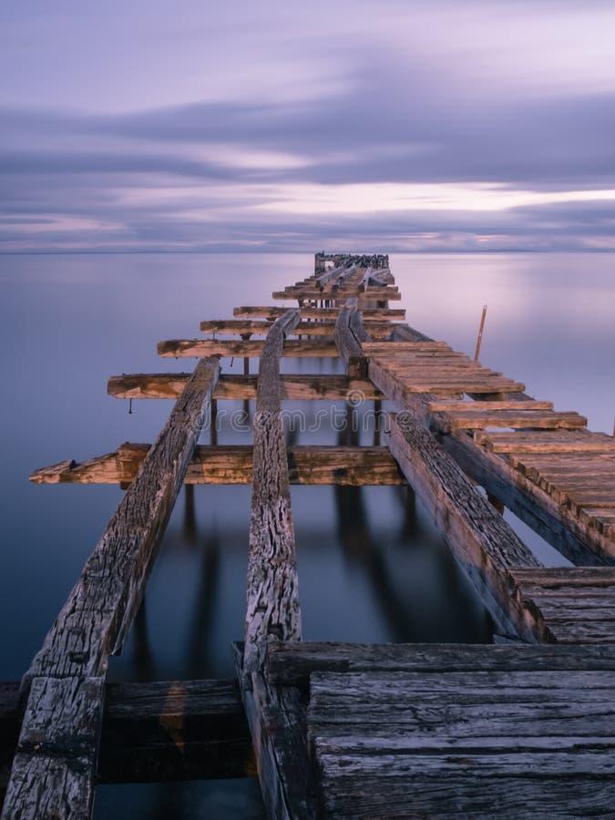 Cais de madeira dividido velho em Punta Arenas, doca velha no Chile no Oceano Pacífico foto de stock