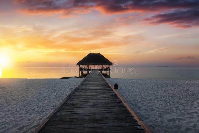 Cais de madeira que conduz a um alojamento da água nas ilhas de Maldivas fotos de stock