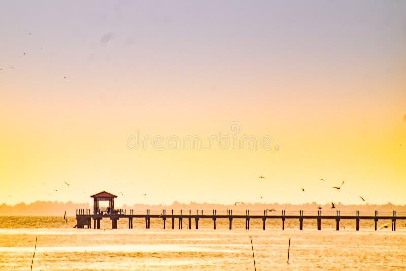 Cais de madeira velho da ponte ninguém contra o céu bonito do por do sol da natureza, o fundo natural, o contexto e o voo do segu imagens de stock royalty free