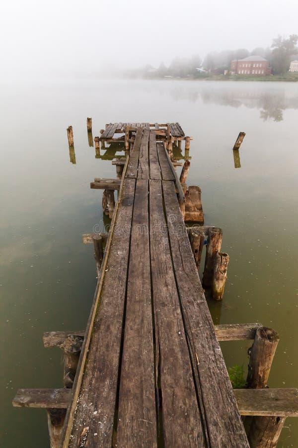 Cais de madeira velho em um lago enevoado fotos de stock royalty free