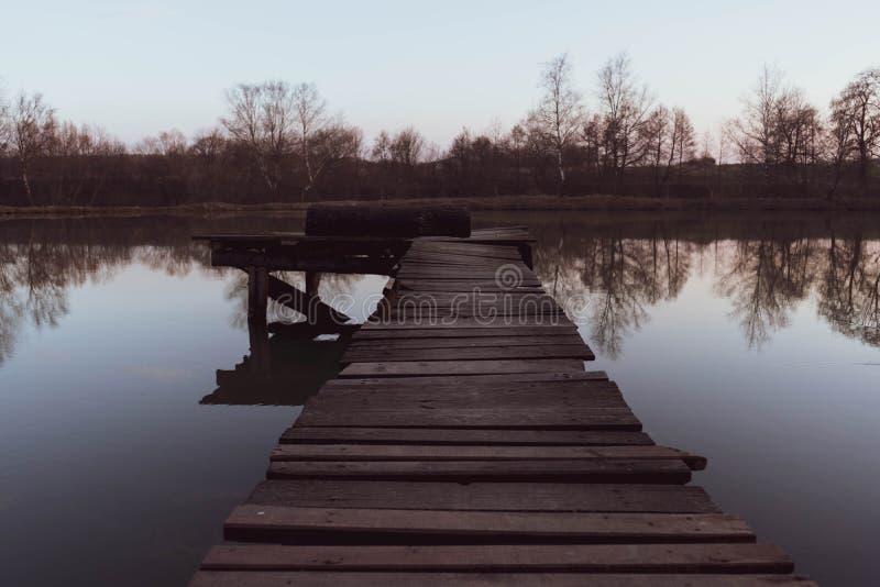 Cais de madeira velho na lagoa bonita pequena no por do sol imagens de stock royalty free