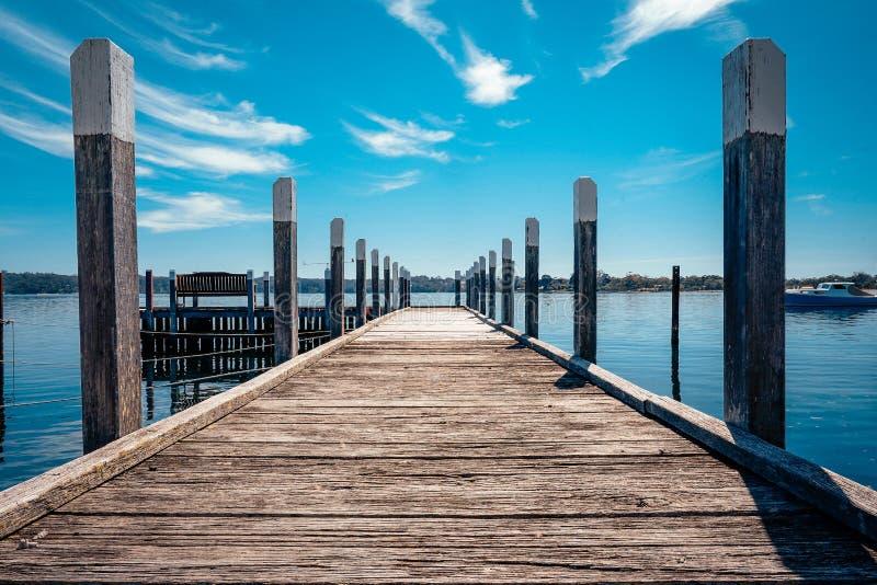 Cais de madeira velho que conduz ao lago com o céu nebuloso azul imagens de stock royalty free