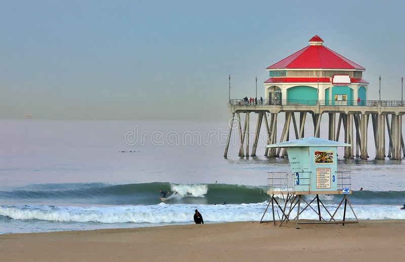 Cais e surfista de Huntington Beach no alvorecer imagem de stock