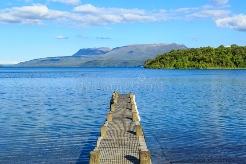 Cais no lago Tarawera, Nova Zelândia, com montagem Tarawera no fundo fotografia de stock