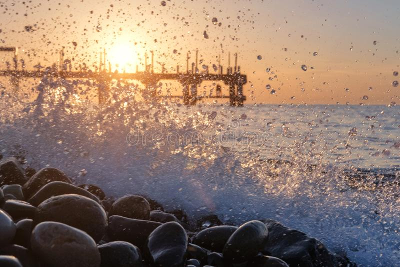 Cais no por do sol atrás de espirrar ondas fotos de stock