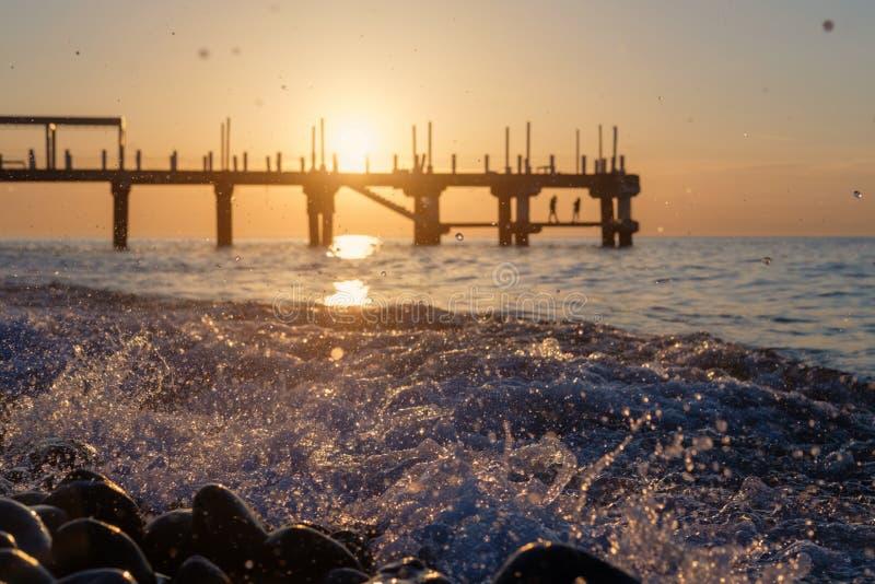 Cais no por do sol atrás de espirrar ondas foto de stock royalty free