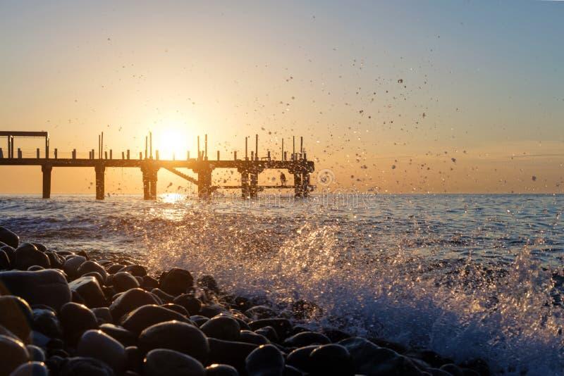 Cais no por do sol atrás de espirrar ondas fotografia de stock