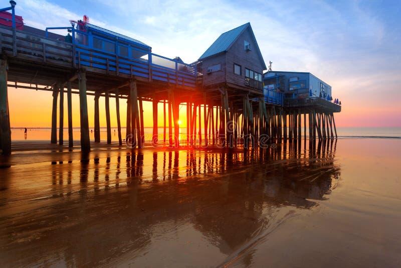 Cais velho da praia do pomar no nascer do sol fotografia de stock