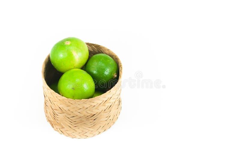 Cais verdes frescos na cesta de bambu isolada no fundo branco imagem de stock royalty free