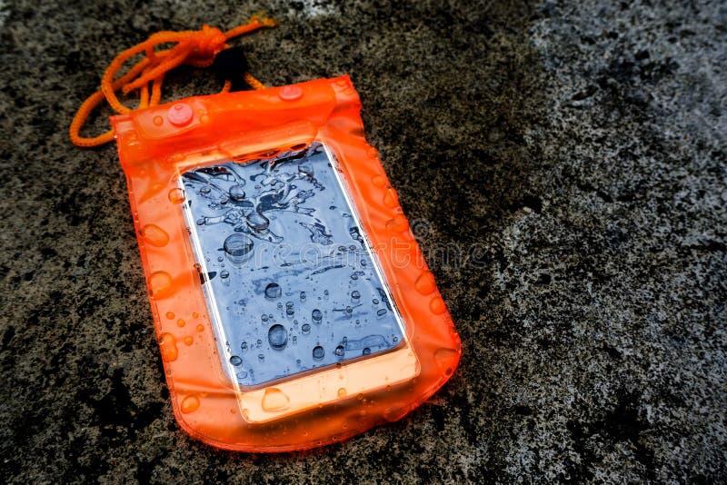 Caisse imperméable orange de téléphone portable avec des gouttelettes d'eau Sac de serrure de fermeture ?clair de PVC prot?ger le photo stock