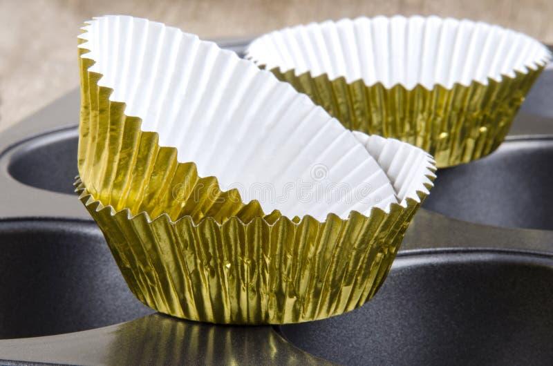 Caisses de gâteau de cuvette d'or sur un bidon de traitement au four photographie stock libre de droits