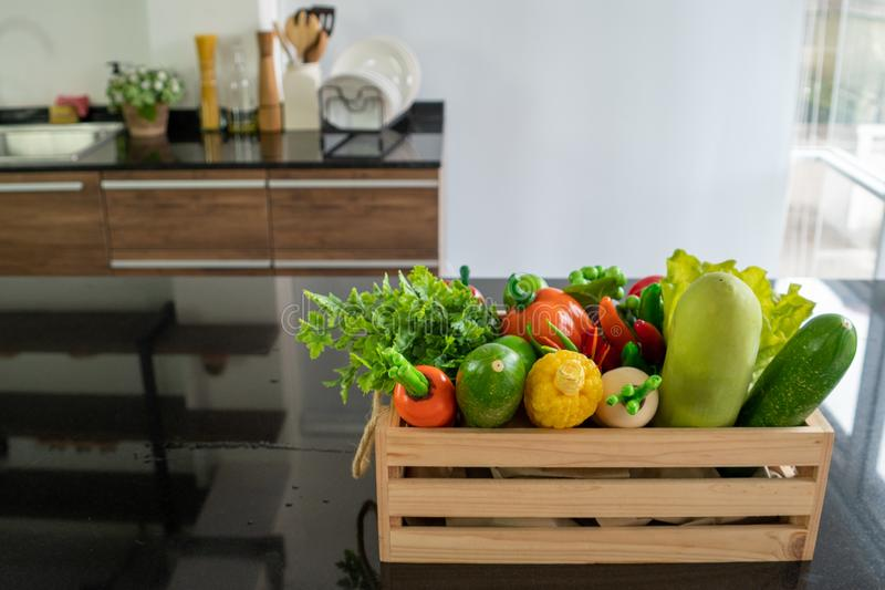 Caisses en bois remplies de divers genres de légumes frais placés sur le compteur dans la cuisine photos stock
