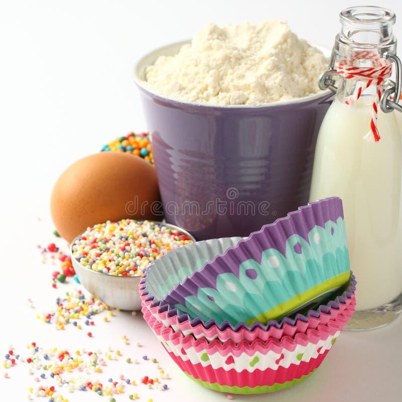 Caisses et ingrédients de petit gâteau au-dessus de blanc avec le copyspace images stock