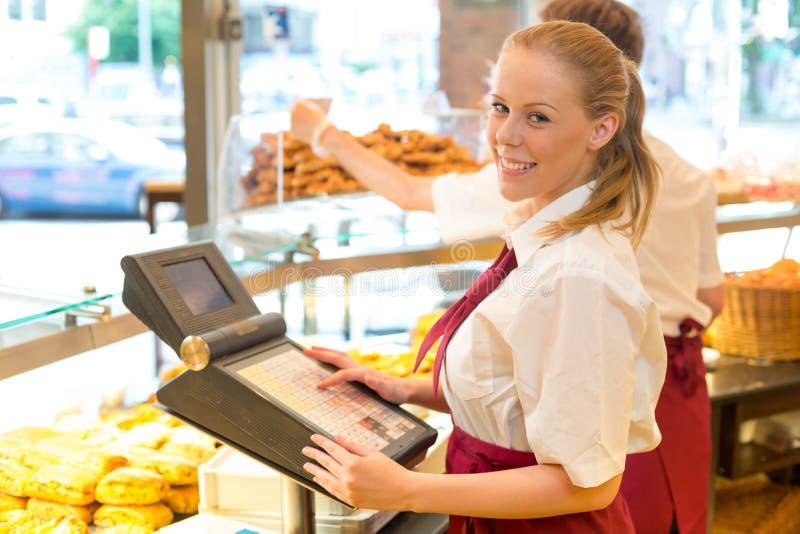 Caissier dans la boutique du boulanger posant avec la caisse enregistreuse photographie stock