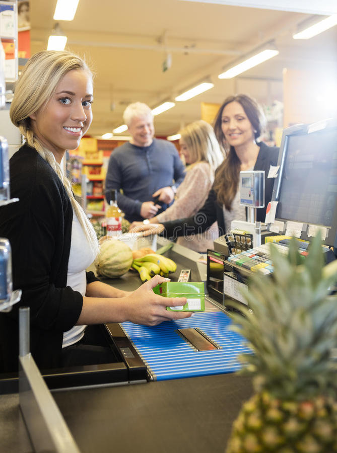 Caissier sûr Holding Juice Packet At Checkout Counter au Su images stock