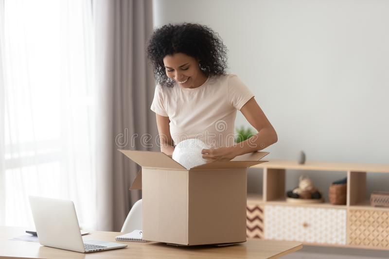 Caixa aberta satisfeita feliz do pacote do cliente preto da menina em casa fotos de stock royalty free
