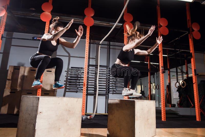 Caixa apta da jovem mulher que salta em um gym apto da cruz imagens de stock