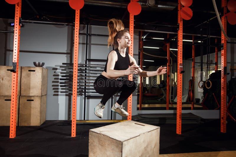 Caixa apta da jovem mulher que salta em um gym apto da cruz imagem de stock royalty free