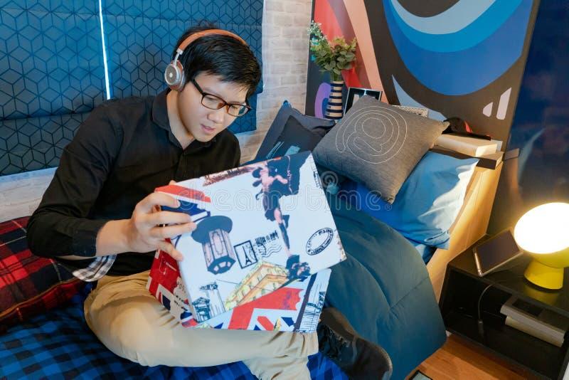 Caixa asiática da abertura do homem que senta-se no quarto imagens de stock