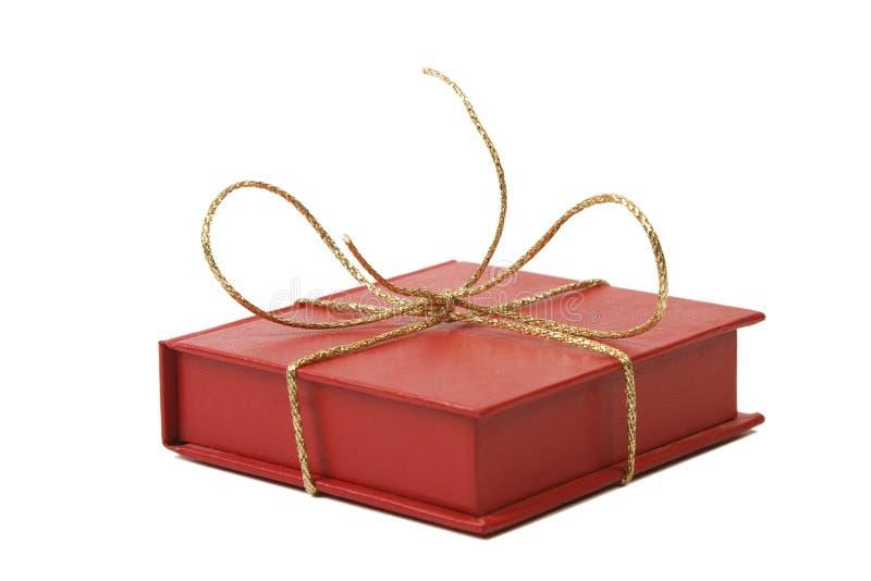 Caixa atual do vermelho com a fita brilhante dourada imagem de stock