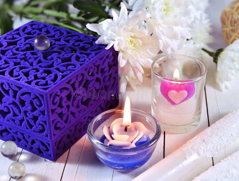 Caixa azul com duas velas e flores imagem de stock royalty free