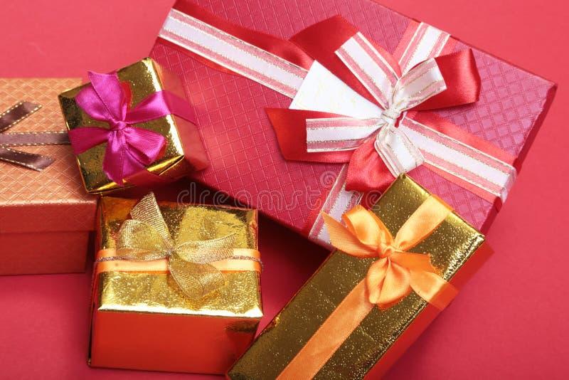 Caixa bonita do presente do ouro com curva vermelha e fitas no backgound fotografia de stock