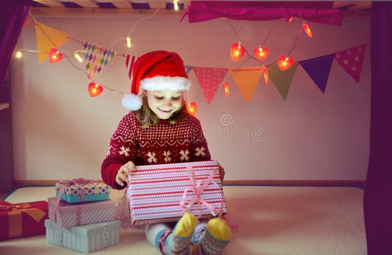 Caixa bonito da abertura da menina com presente de Natal fotos de stock