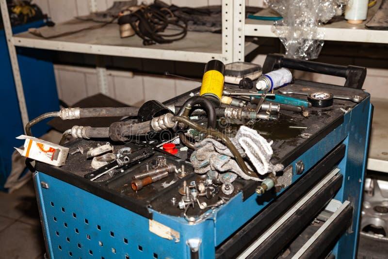 Caixa com as ferramentas e as peças sobresselentes que encontram-se nela na desordem em processo de reparar o carro na oficina pa imagem de stock royalty free