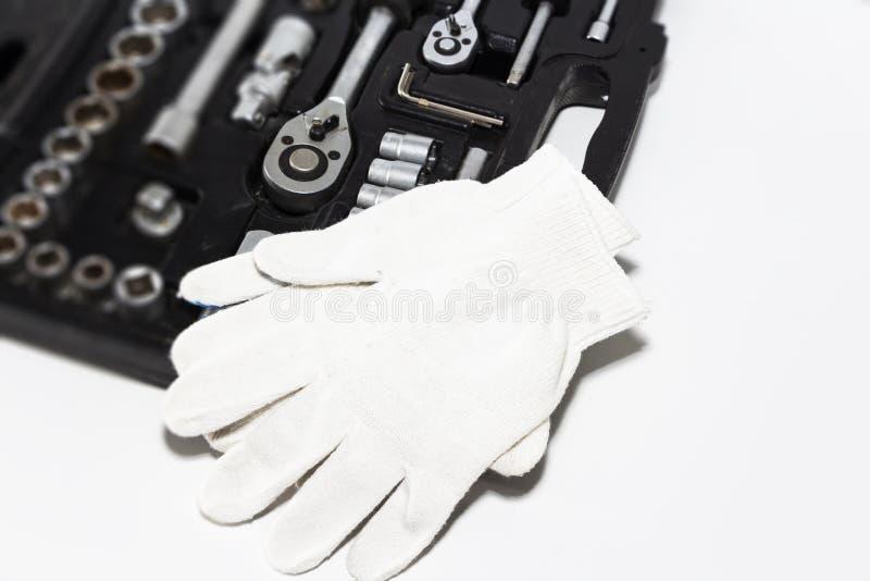 Caixa com ferramentas e luvas do trabalho em uma oficina de reparações do carro, close-up Ajuste de muitas ferramentas do vanádio fotos de stock
