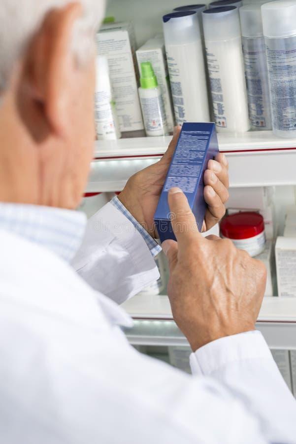 Caixa da medicina de Reading Instructions On do farmacêutico na farmácia imagens de stock